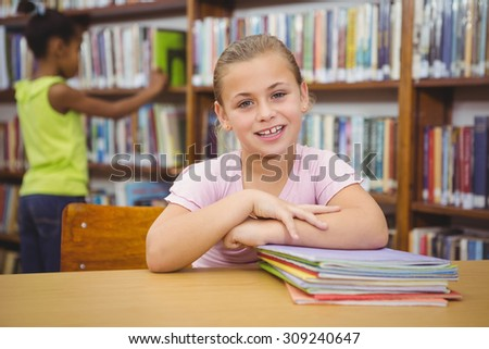 Smiling student sitting at a table at the elementary school