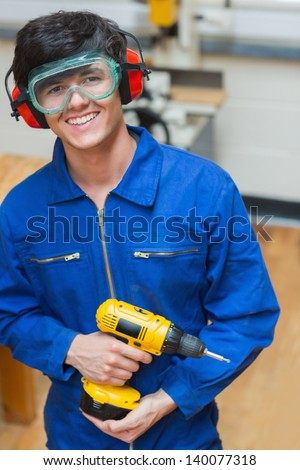 Smiling student standing in a woodwork class and holding a driller - stock photo