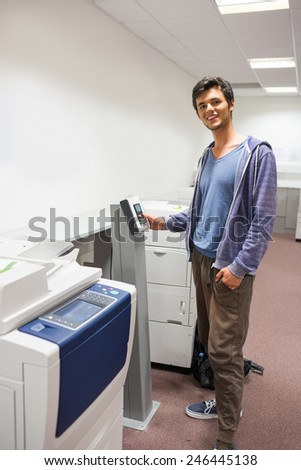 Smiling student standing next to the photocopier at the university - stock photo