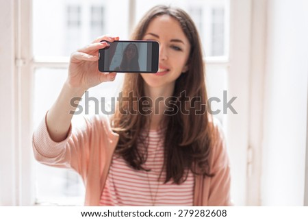 Smiling student taking selfie at hallway