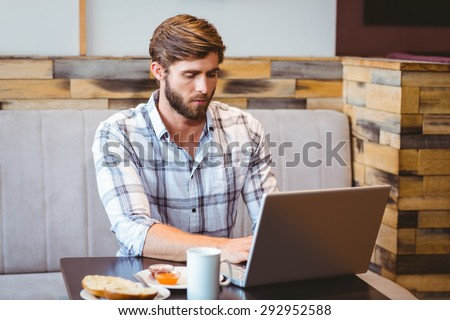 Smiling student using laptop in cafe at the university - stock photo
