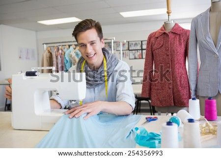Smiling student using sewing machine at the college