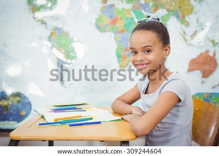 Smiling student with a book on the desk at the elementary school