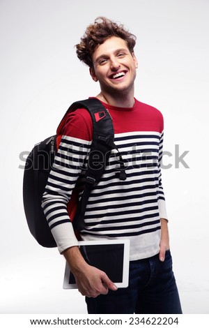 Smiling student with backpack and tablet computer over gray background - stock photo