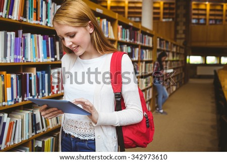 Smiling student with backpack using tablet in library at the university
