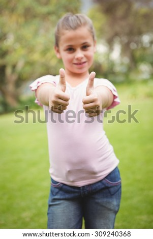 Smiling student with thumbs up on the school grounds - stock photo