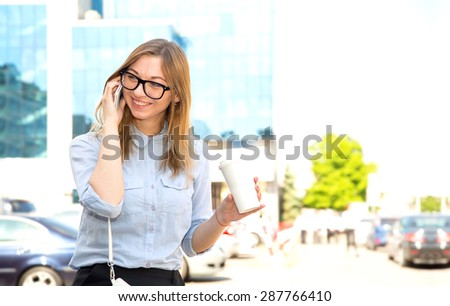 Smiling student woman in glasses. Business woman professional walking outdoors. She is talking on cell phone and drinking coffee from disposable paper cup. Multiracial, asian, american, caucasian lady - stock photo