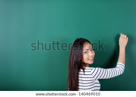 smiling student writing on empty blackboard looking back over shoulder - stock photo