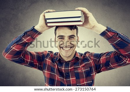 Smiling student young man holding books on his head over grey background. - stock photo