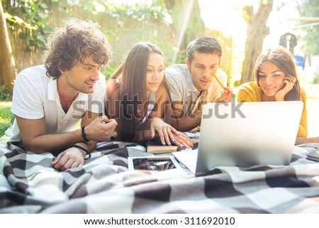 Smiling students doing homework on the laptop together outdoors - stock photo
