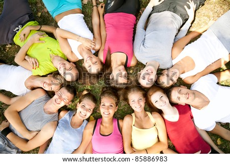 smiling students lying on grass with their heads in a circle