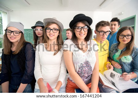 Smiling students posing in a classroom wearing glasses - stock photo