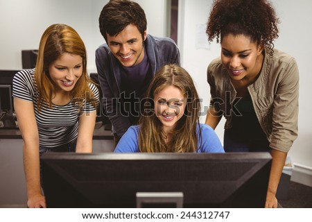 Smiling students sitting at desk using computer together in classroom
