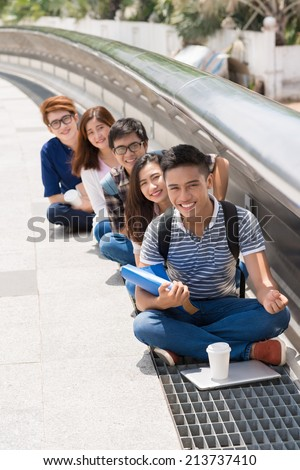 Smiling students sitting in a row and looking at the camera - stock photo