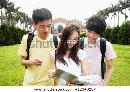 smiling students standing together with books at a campus