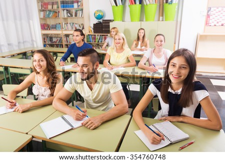 Smiling students studying in the classroom - stock photo