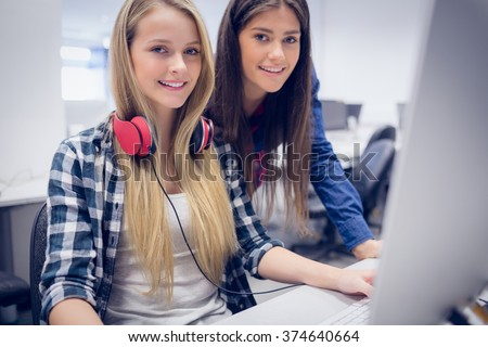 Smiling students using computer at university - stock photo
