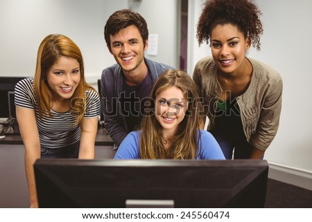 Smiling students using computer together looking at camera in classroom - stock photo