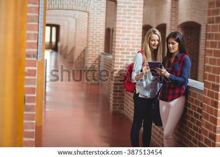 Smiling students using tablet together at university - stock photo