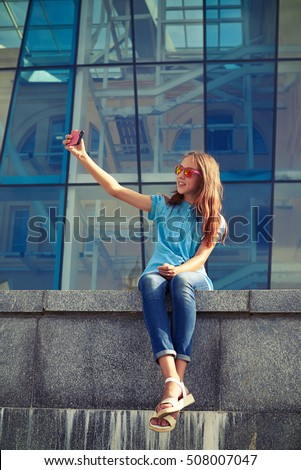 Smiling stylish girl is taking selfie against business center in the downtown