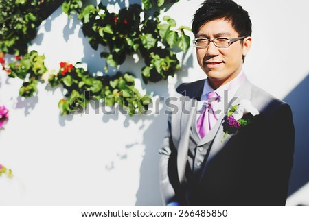 smiling stylish happy asian groom stands near wall and green leaf on a sunny day before wedding ceremony in island Santorini