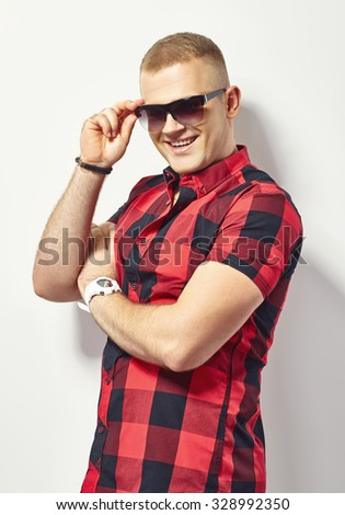 Smiling stylish man in hipster plaid shirt and sunglasses  - stock photo