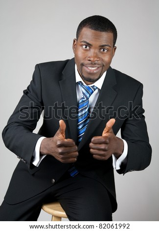 Smiling successful African American businessman with thumbs up.