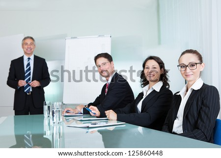 Smiling successful business team holding a meeting sitting around a white glass topped table with one executive - stock photo