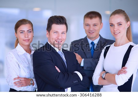 Smiling successful business team standing in office . - stock photo