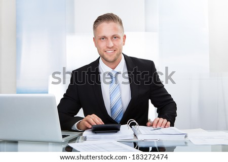 Smiling successful businessman sitting st his desk in the office surrounded by paperwork using a calculator and a laptop - stock photo
