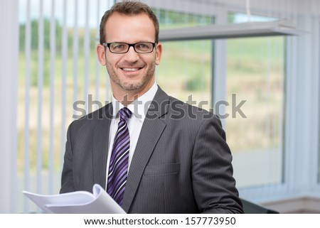 Smiling successful businessman wearing glasses holding a document in his hand looking at the camera with a confident smile - stock photo