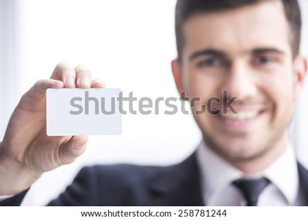 Smiling successful businessman with  business card or sign. In the foreground a business card with a blurred background. - stock photo