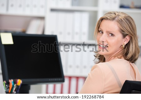 Smiling successful businesswoman sitting at her desk in the office in front of a desktop monitor turning to give the camera a happy smile - stock photo
