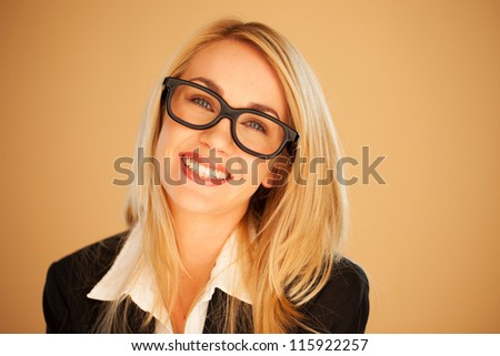 Smiling successful businesswoman wearing glasses, head portrait on a brown studio background