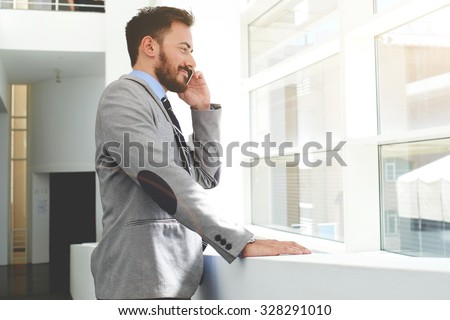 Smiling successful man financier dressed in luxury clothes talking on his mobile phone while standing in modern office, young cheerful businessman having cell telephone conversation with copy space - stock photo