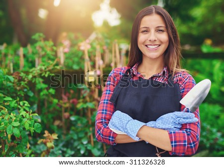 Smiling successful young nursery owner standing amongst her plants with folded arms and a trowel in her hands beaming at the camera - stock photo
