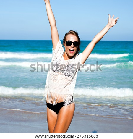 smiling summer girl,with blond hair and swimsuit,laughing and smiling , summer mood , cheerful girl on the sea, red lips , natural makeup, summer black sunglasses - stock photo