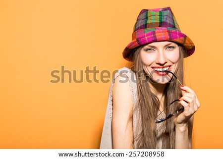 Smiling summer woman with hat and sunglasses over bright background. studio shot, copy space - stock photo