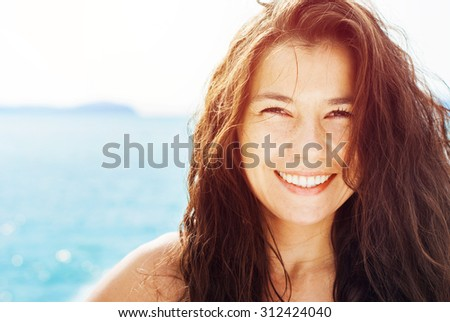 Smiling Suntanned Woman On the Background by Blue Sea in Sunlight. Summer day - stock photo