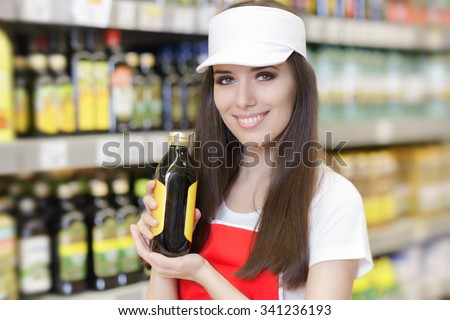 Smiling Supermarket Employee Holding a Product - Portrait of a young sales clerk in a market store