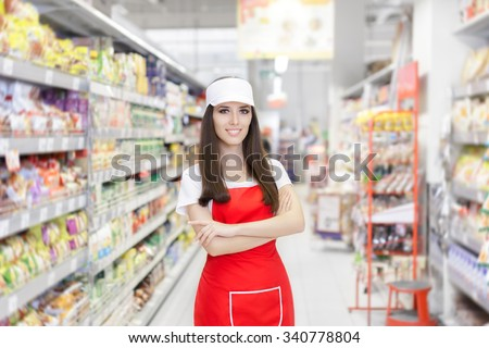 Smiling Supermarket Employee Standing Among Shelves - Portrait of a young sales clerk in a market store   - stock photo