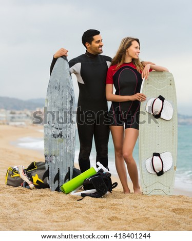 Smiling surfers family on the beach in wetsuits - stock photo
