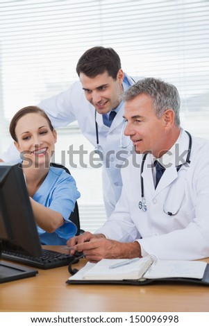 Smiling surgeon working with doctors on computer in bright office
