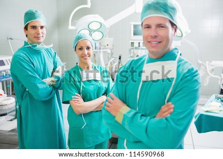 Smiling surgeons looking at camera with crossed arms in an operating theatre - stock photo