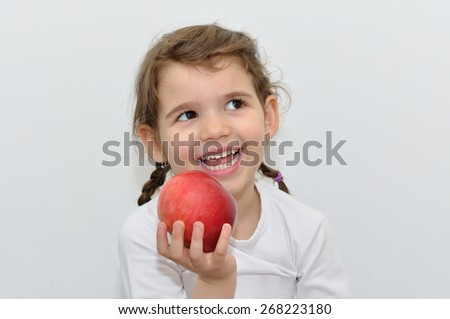Smiling sweet young girl with two pigtails and beautiful white teeth holding  red apple - stock photo