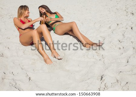Smiling tanned blonde and brunette having beers on the beach