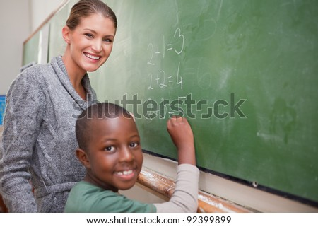 Smiling teacher and a pupil making an addition on a blackboard