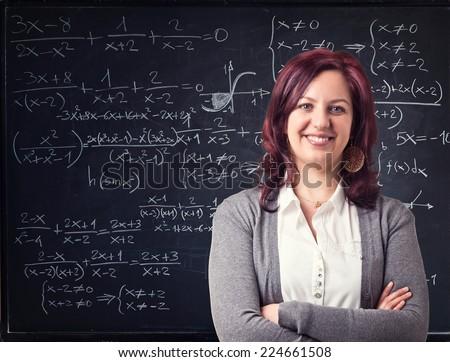 smiling teacher and blackboard background - stock photo