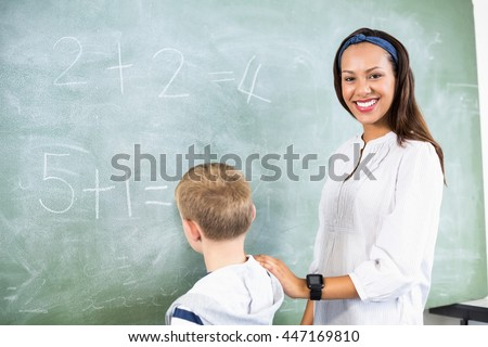 Smiling teacher assisting boy in doing addition on chalkboard in classroom at school - stock photo
