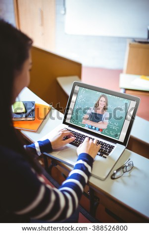 Smiling teacher holding notebook in front of blackboard against happy student in lecture hall using laptop - stock photo